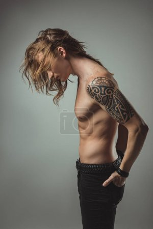 sexy shirtless man with tattoo posing in black jeans, isolated on grey