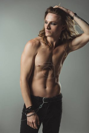 shirtless sexy man with long hair posing in black jeans, on grey