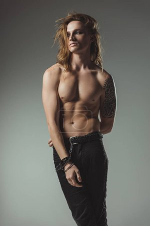 shirtless caucasian man with long hair posing in black jeans, isolated on grey