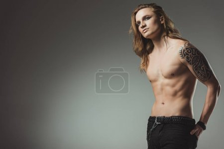 fashionable shirtless man with tattoo posing in black jeans, isolated on grey