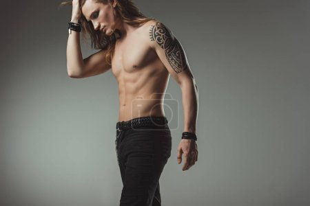 Photo for Stylish shirtless man with tattoo posing in black jeans, isolated on grey - Royalty Free Image