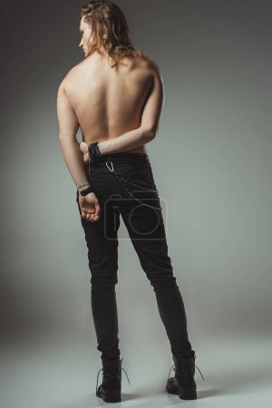 back view of shirtless man standing in black jeans, on grey