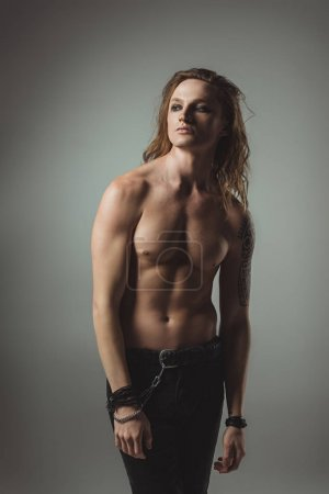 shirtless trendy man with long hair posing in for studio shot, isolated on grey