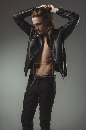 handsome shirtless rocker with long hair posing in black leather jacket, isolated on grey