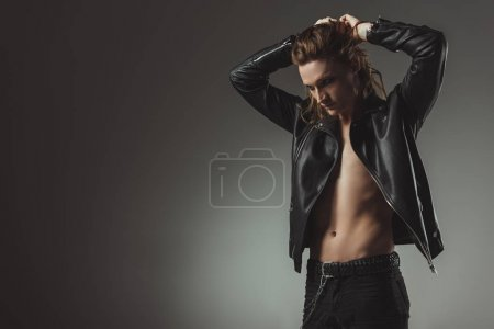 shirtless rocker with long hair posing in black leather jacket, isolated on grey