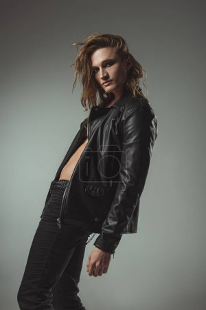 stylish man with long hair posing in black leather jacket, isolated on grey