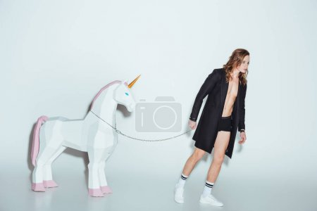 fashionable man in black jacket with big unicorn on chain, on grey