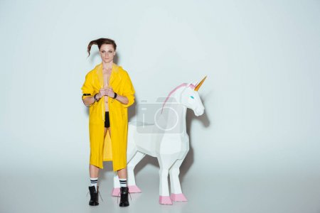 fashionable man with hairstyle in yellow raincoat standing with big unicorn toy, on grey
