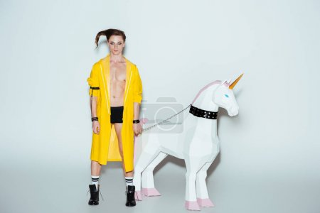 male model in boxer shorts and yellow raincoat standing with big unicorn toy on chain, on grey