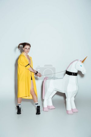 stylish man in yellow raincoat standing with big unicorn toy on chain, on grey