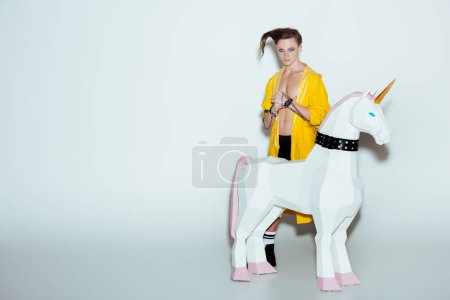 fashionable man with hairstyle in yellow raincoat standing with big unicorn toy in collar, on grey