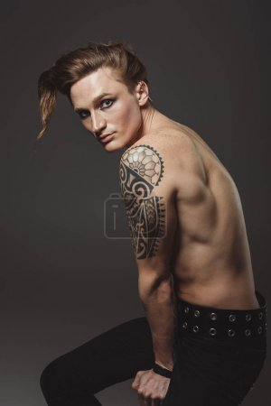shirtless tattooed male model with strange hairstyle, isolated on grey