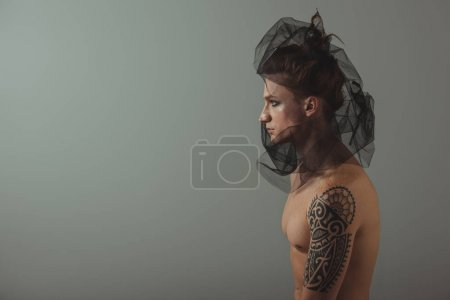 shirtless tattooed man posing with black net on head for fashion shoot, isolated on grey