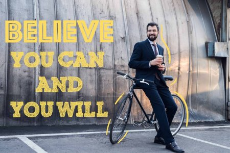 smiling businessman with disposable cup of coffee leaning on bicycle on street with believe you can and you will