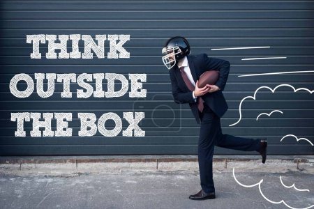 Photo for Side view of businessman in suit and rugby helmet with ball in hands running on street with think outside box inscription - Royalty Free Image