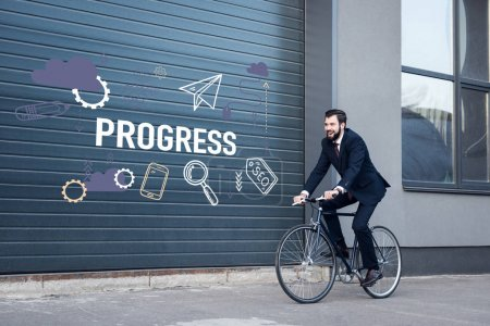 smiling young businessman in suit riding bicycle on street with progress inscription and business icons on gate entrance