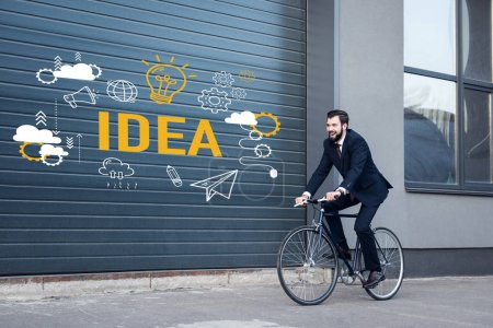 smiling young businessman in suit riding bicycle on street with idea inscription and business icons on gate entrance