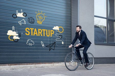 smiling young businessman in suit riding bicycle on street with startup inscription and business icons on gate entrance