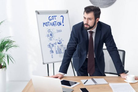 pensive businessman looking away at workplace in office with got motivation inscription and business graphs on whiteboard
