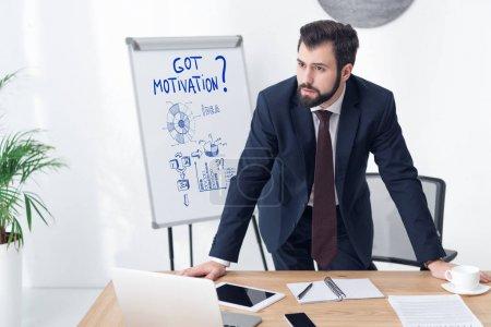 Foto de Empresario pensativo mirando lejos trabajo en oficina con tiene motivación inscripción y negocios gráficos de pizarra - Imagen libre de derechos