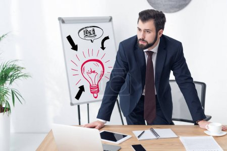 pensive businessman looking away at workplace in office with idea inscription and light bulb icon on whiteboard