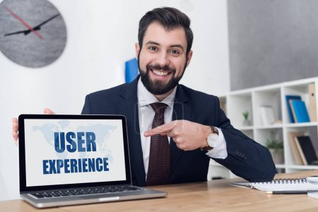 portrait of cheerful businessman pointing at laptop with user experience inscription at workplace in office