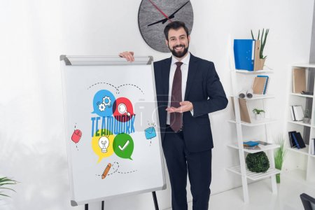 smiling businessman pointing at whiteboard with teamwork inscription and business icons in office