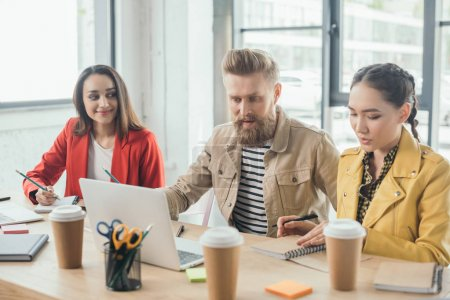 Diverse women and man working on business project by laptops in light office