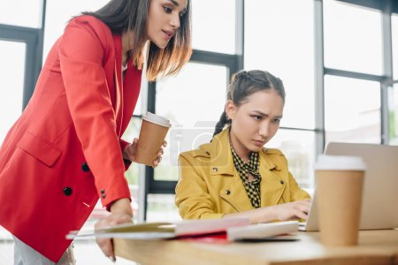 Photo for Professional businesswomen looking at laptop screen in modern office - Royalty Free Image