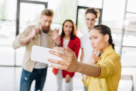 Close-up view of smartphone in hand on woman taking selfie with her business team in modern office