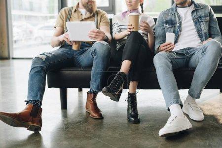 Vista recortada de gente de negocios descansando y sosteniendo gadgets en la oficina de luz moderna