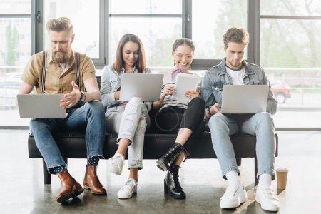 Des hommes d'affaires prospères qui travaillent avec des appareils numériques dans un bureau moderne