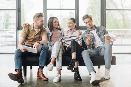 Des collègues d'affaires souriants hommes et femmes se détendre dans un bureau moderne