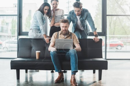 Professional business people looking at their male colleague working on laptop in modern office