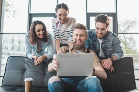Diverse business team looking at laptop in light workspace