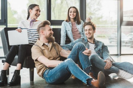 Successful business people sitting and resting together in modern light office