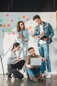 Successful business people looking at their male colleague working on laptop in modern light office