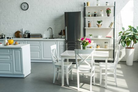 Photo pour Intérieur de cuisine lumineuse moderne avec table et chaises - image libre de droit