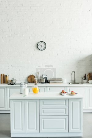 Photo for Interior of modern light kitchen with pancakes and orange juice on kitchen counter - Royalty Free Image