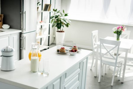 interior of modern light kitchen with pancakes on kitchen counter
