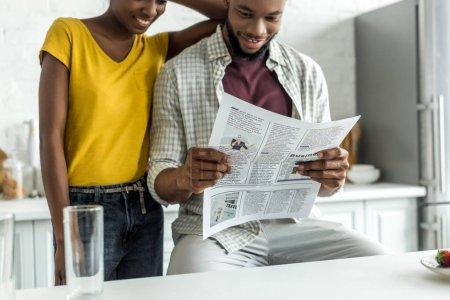 Cropped image de couple afro-américain, lecture de journaux à la cuisine
