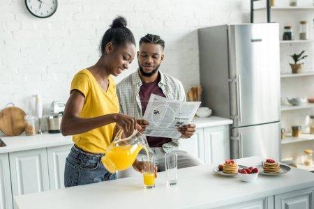 copain afro-américaine, lire le journal et sa petite amie, verser le jus d'orange dans le verre à la cuisine