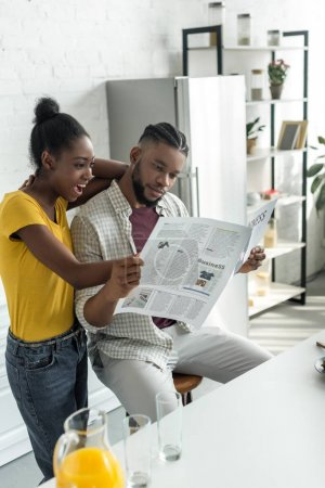 african american couple reading newspaper at kitchen