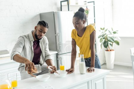 Photo for African american boyfriend pouring out cornflakes into plate at kitchen - Royalty Free Image