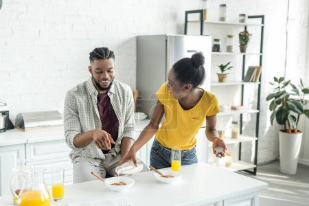african american girlfriend pouring milk into boyfriend plate at kitchen