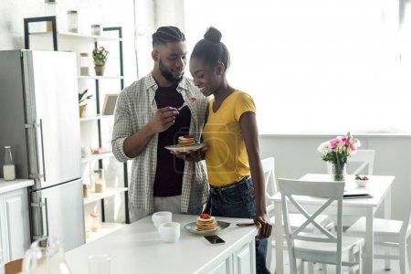 african american boyfriend feeding girlfriend with strawberry at kitchen