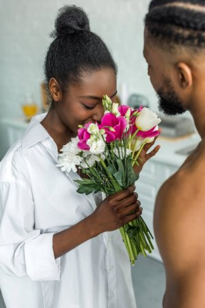 african american girlfriend sniffing flowers at kitchen