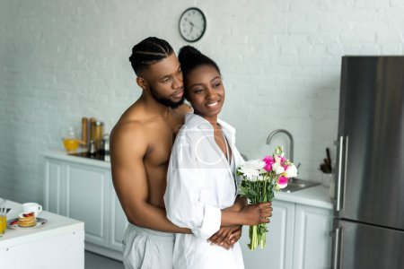 african american boyfriend hugging girlfriend and they looking away at kitchen