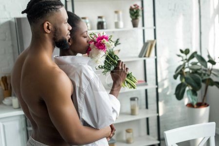 african american boyfriend hugging girlfriend and she sniffing bouquet of flowers at kitchen