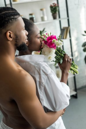 african american boyfriend hugging girlfriend and she sniffing flowers at kitchen